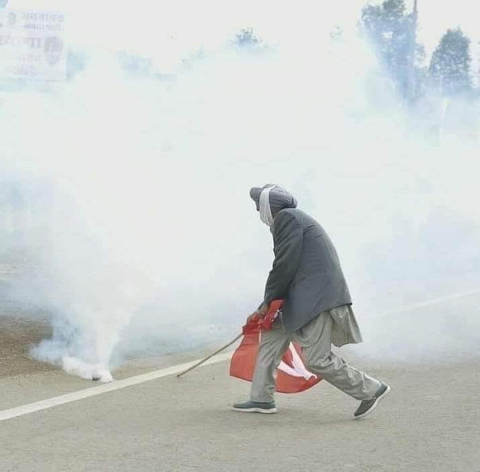 Dharampal Seel, ein hochrangiger Kisan Sabha-Führer aus dem Punjab, benutzt seine rote Flagge, um einen Tränengaskanister zu entfernen, 27. November 2020.